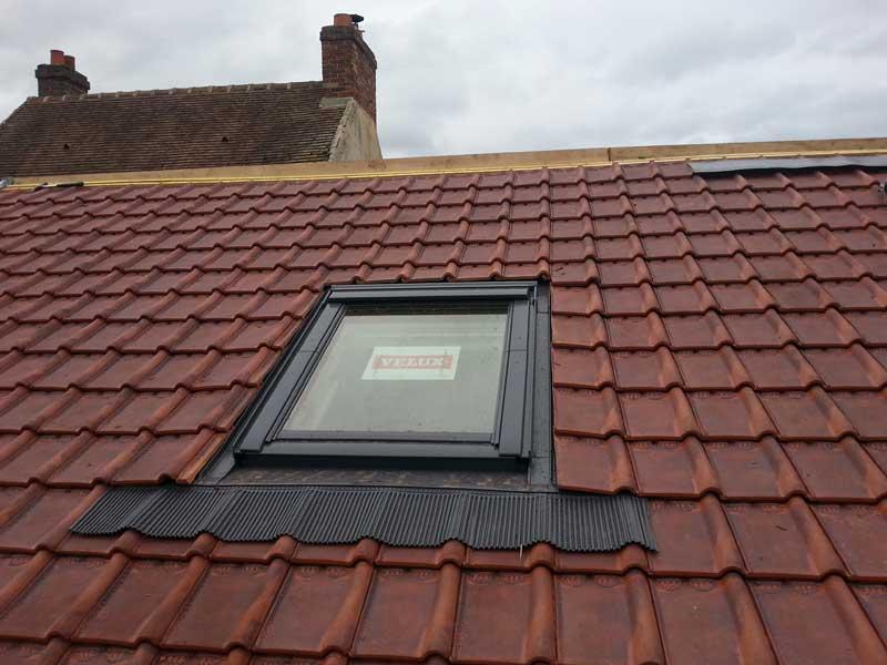 Une fenêtre de toit rénovée et posée sur toit
